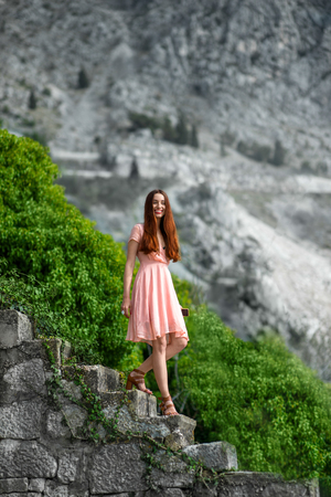 pink dress: Young woman in pink dress going down stairs with beautful nature background in the old city
