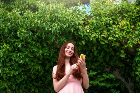pink dress: Young woman in pink dress using mobile phone on green ivy background