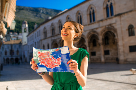 Young woman in green dress looking for sightseeing holding map of Dubrovnik old city center