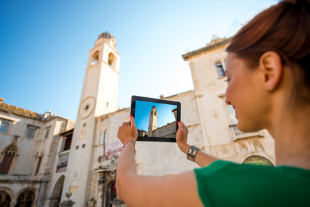 ragusa: Young woman traveler photographing clock tower with digital tablet in Dubrovnik old city center.