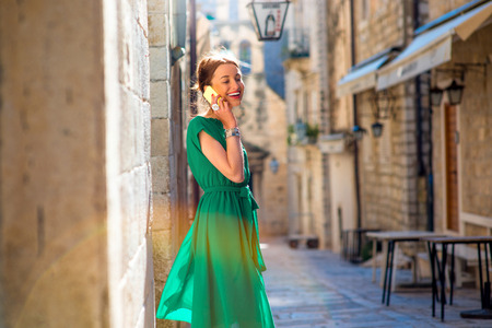 ragusa: Young woman in beautiful green dress using mobile phone walking on the old city street in Dubrovnik, Croatia Stock Photo