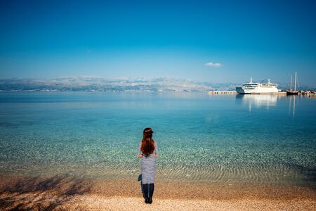 Woman looking at ferry on the beach of Brac island