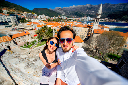 self   portrait: Young couple taking self portrait on old city background in Budva, Montenegro Stock Photo