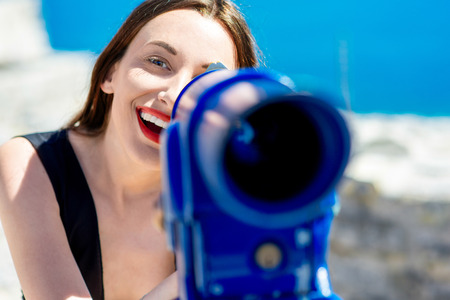 keek: Young woman traveler looking at camera  through a blue telescope outdoor near the sea