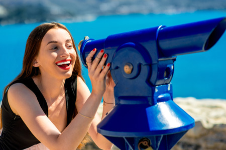 keek: Young woman traveler looking through a blue telescope outdoors near the sea Stock Photo