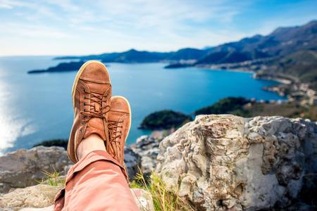 piernas: Piernas para hombre de los zapatos marrones que mienten en la monta�a en el fondo mar escapo Foto de archivo