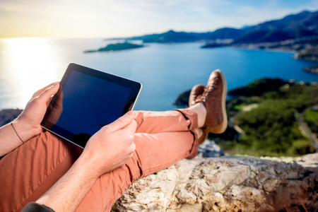 Man holding digital tablet on the mountain top on the sea scape background Imagens