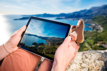people and nature: Man holding digital tablet on the mountain top on the sea scape background Stock Photo