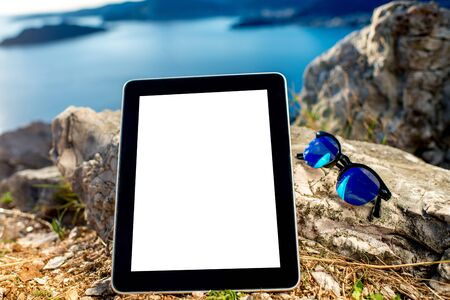 e pretty: Digital tablet with empty screen and sunglasses on the rock mountain with sea scape background Stock Photo