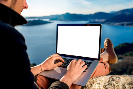 Man working with laptop on the top of mountain with beautiful landscape on background. Stock Photo