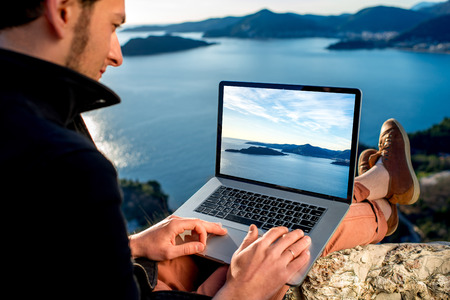 Man working with laptop on the top of mountain with beautiful landscape on background. Banco de Imagens