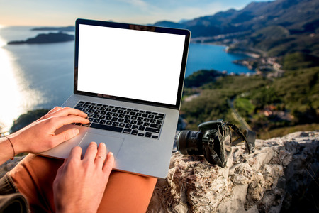 Man working with laptop on the top of mountain with beautiful landscape on background. Фото со стока