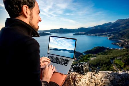 배경에 아름 다운 풍경과 산 꼭대기에 노트북을 사용하는 사람.