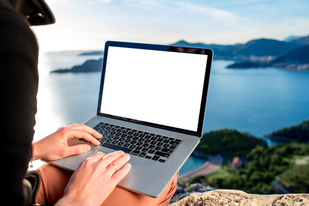 Man working with laptop on the top of mountain with beautiful landscape on background. Banque d'images