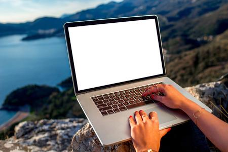 persona escribiendo: Mujer que trabaja con la computadora portátil en la parte superior de la montaña con hermoso paisaje en el fondo. Concepto Blogging Foto de archivo