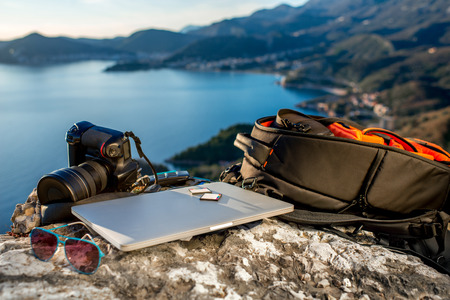 backpack: Travel photographer equipment on rocky mountain with beautiful landscape on the background
