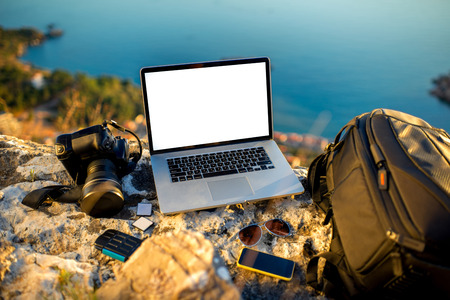 carryall: Travel photographer equipment on rocky mountain with beautiful landscape on the background