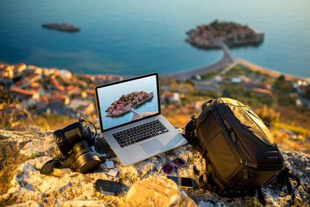 Reisfotograaf apparatuur op rotsachtige berg met prachtige landschap op de achtergrond