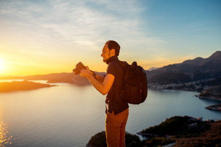 staring at the camera man: Photographer with professional photo camera and backpack on the top of the mountain on the beautiful sunset. Stock Photo