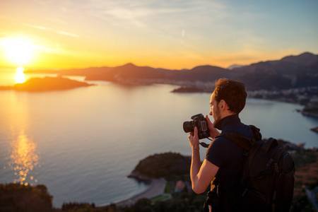 nature picture: Photographer with professional photo camera and backpack on the top of the mountain on the beautiful sunset. Stock Photo