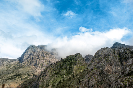 blanketed: Rocky mountains blanketed in the clouds in Montenegro