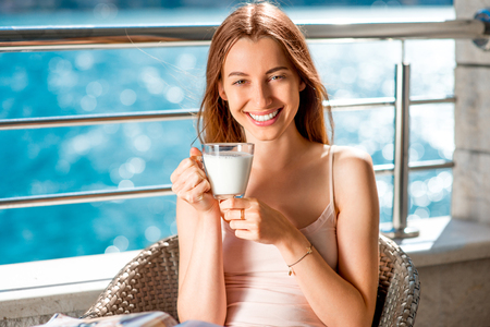 good shirt: Young and smiling woman drinking milk on the balcony on blue water