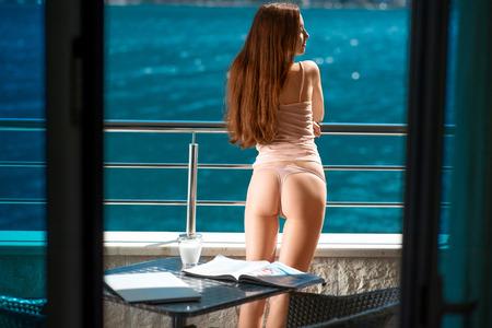 culo: Sexy donna in piedi sul balcone e godersi bellissima vista sul mare Archivio Fotografico
