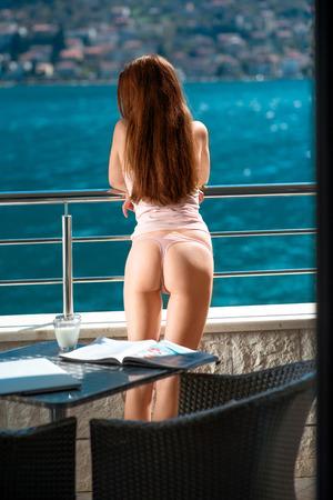 sexy woman standing: Sexy mujer de pie en el balc�n y disfrutar de hermosa vista sobre el mar