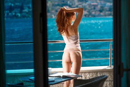バルコニーの上に立って、海の美しい景色を楽しみながらのセクシーな女性