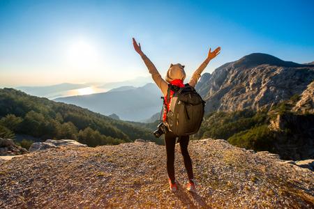 Jeune photographe voyageur avec appareil photo et sac à dos debout sur le sommet de la montagne et à la recherche sur le coucher de soleil