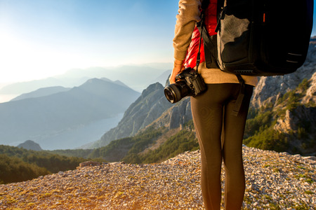 Young traveler photographer with photo camera and backpack standing on the top of mountain. Focused on the photo camera photo