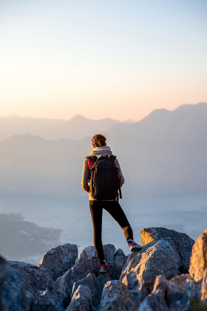 locality: Young traveler with backpack standing on the big stones on the mountain and observing locality Stock Photo