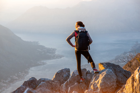 バックパック山と観察地域に大きな石の上に立っての若い旅行者 写真素材