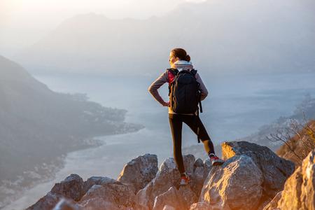 persona de pie: Viajero joven con mochila de pie en las grandes piedras en la montaña y observar localidad
