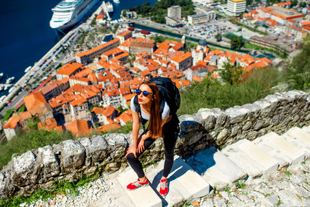Young woman traveler with backpack climbing up Lovcen mountain near the old city Kotor, Montenegro photo