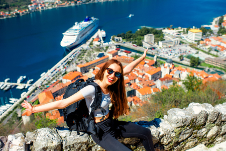 Young woman traveler with backpack sitting on Lovcen mountain near the old city Kotor, Montenegro photo