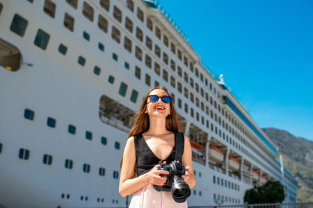 cruise: Young woman tourist photographing near the big cruise liner