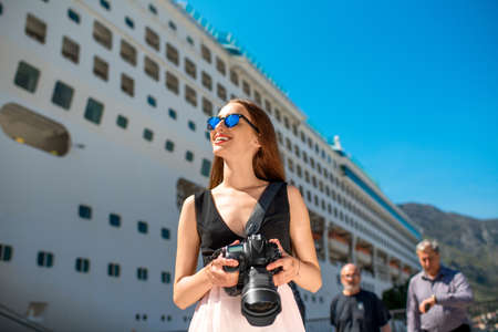 cruise liner: Young woman tourist photographing near the big cruise liner