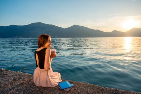 mujer tomando cafe: Joven mujer sentada con la taza de café en el muelle al amanecer con bellas montañas y el mar en el fondo