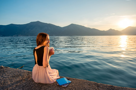 Young woman sitting with coffee cup on the pier at sunrise with beautiful mountains and sea on background