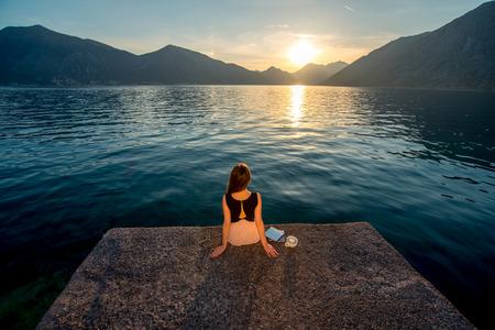 jezior: Samotna kobieta marzy i patrząc na piękny wschód słońca na molo z widokiem na morze i góry w tle. Widok z tyłu, plan ogólny Zdjęcie Seryjne