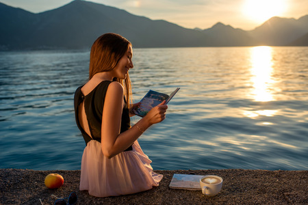 girl apple: Young woman reading book and looking at beautiful sunrise on the pier with sea and mountains on background