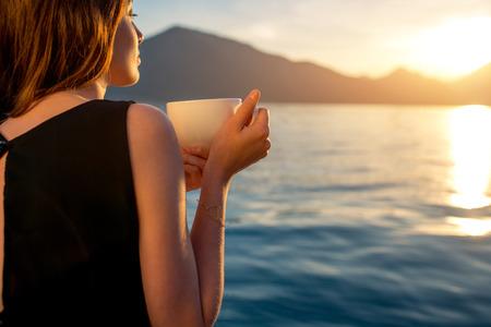 Jonge vrouw genieten van koffie op de pier bij zonsopgang met de bergen op de achtergrond