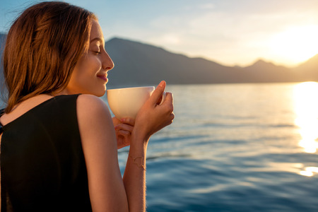 late summer: Young woman enjoying coffee on the pier at sunrise with mountains on background Stock Photo