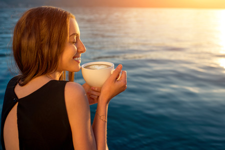 Young woman enjoying coffee on the pier at sunrise with sea on background