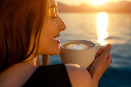 Young woman enjoying coffee on the pier at sunrise with mountains on background Banco de Imagens