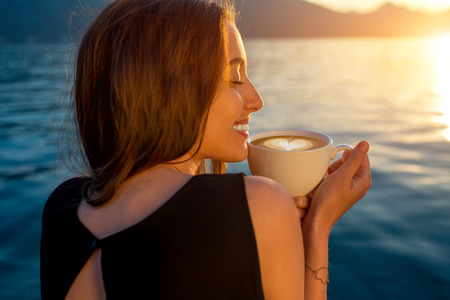Young woman enjoying coffee on the pier at sunrise with mountains on background photo