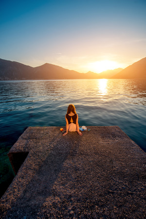 Lonely woman dreaming and looking at beautiful sunrise on the pier with sea and mountains on background. Back view, general plan photo