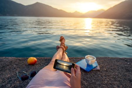 Femme tenant téléphone couché sur la jetée au beau coucher de soleil