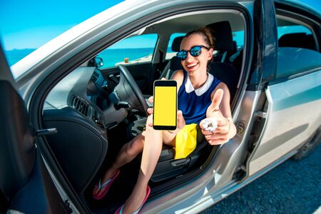 car navigation: Young and cute woman showing phone screen sitting in the car. Navigation or travel phone program concept.